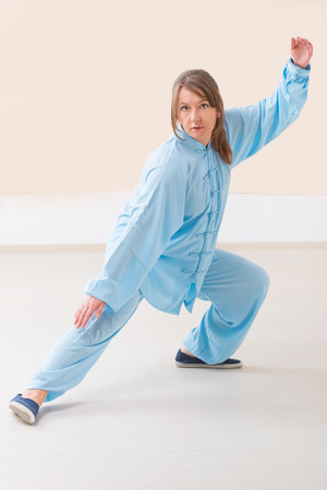 31946188 - beautiful woman doing qi gong tai chi exercise wearing professinal, oryginal chinese clothes at gym